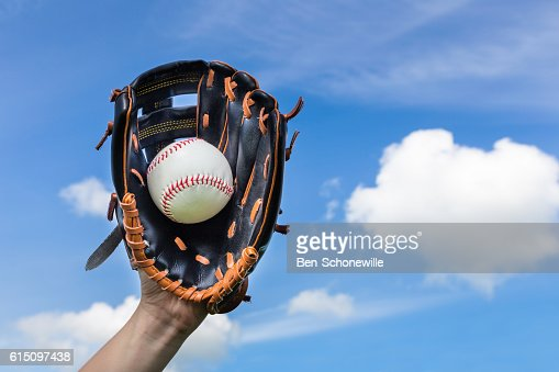 Hand holding baseball in glove with blue sky : Stock Photo