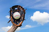 Female hand holding baseball in glove with blue sky. On this sunny day in summer season this person likes to play sport. With one hand wearing a baseball glove and catching the ball in the blue sky. C