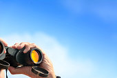 ้hand holding binoculars on blue sky background