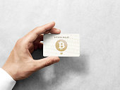 Hand holding bitcoin card template with embossed gold logo. Plain plastic cryptocurrency payment-card display front, design mock up. Electronic wallet mining template.