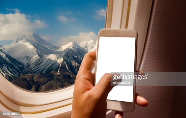 hand holding blank screen smart-phone on board of airplane near window seat and wing with Alps mountain range