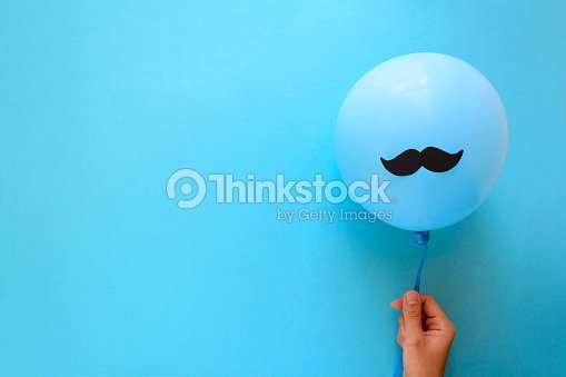 Hand holding blue balloon with a paper mustache on blue paper background. Cut out style. Movember  or man health concept. Top view. Flat lay. Copy space : Foto de stock