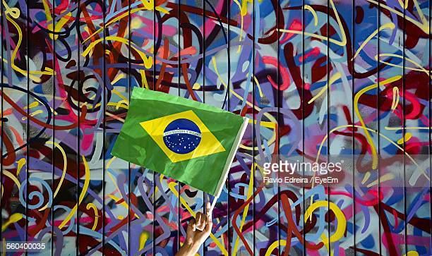 Hand Holding Brazilian Flag Against Colorful Wall