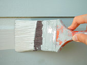 Hand holding brush painting timber wall