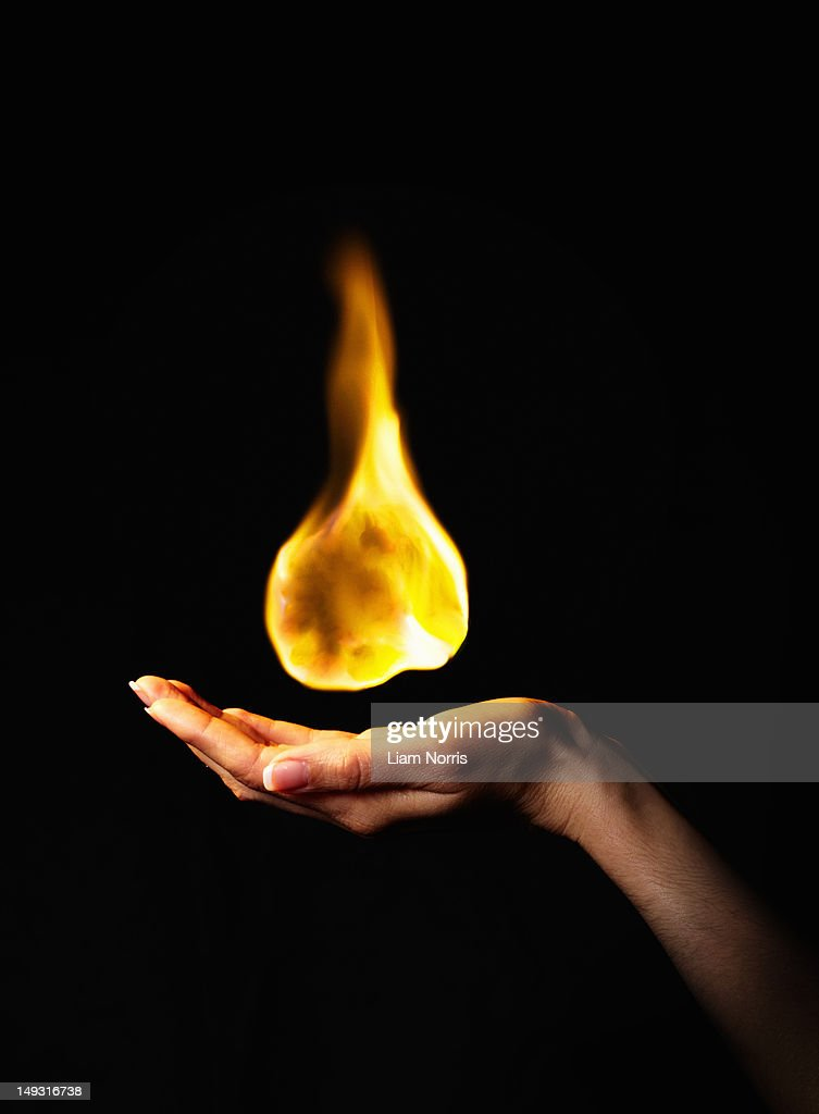 Hand holding burning flame