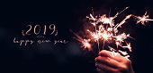 Hand holding burning Sparkler blast with happy new year 2019 on a black bokeh background at night,holiday celebration event party,dark vintage tone