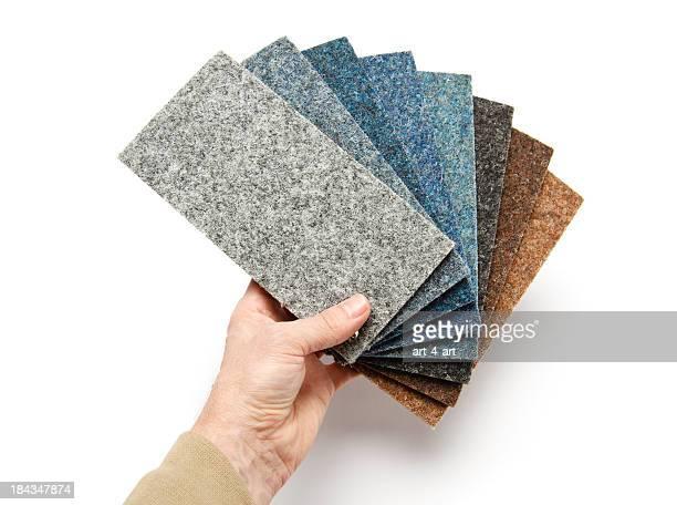 Hand holding Teppich Proben