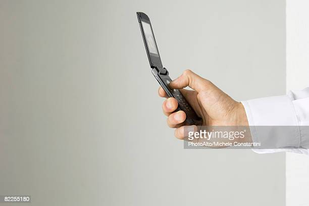 Hand holding cell phone, side view