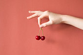 Hand holding cherries on red background , healthy raw food concept