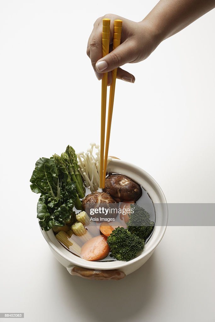 hand holding chopsticks in clay pot of vegetables : Stock Photo