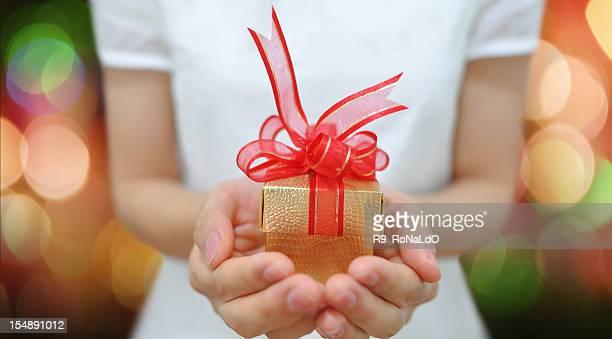 Mano che tiene un regalo di Natale e Capodanno