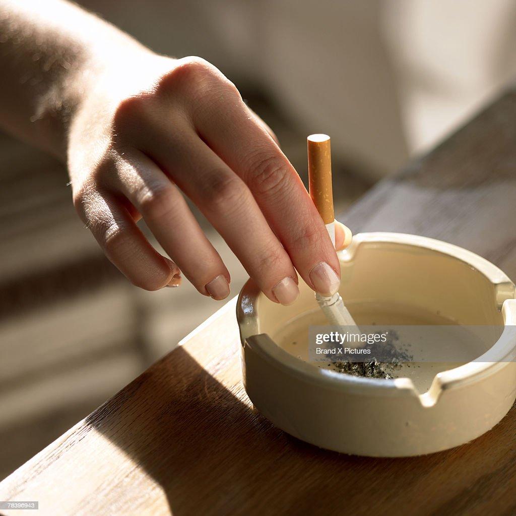 Hand holding cigarette in ashtray : Stock Photo