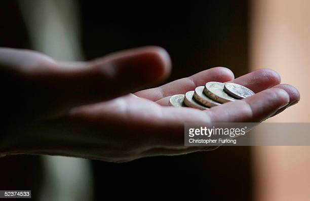 A hand holding coins on March 11 2005 in Glasgow Scotland As of October 2005 the UK minimum wage will be raised to GBP505 from GBP485 while 18 to 21...