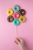 Hand holding colorful donuts on pink background. Colorful creative concept.