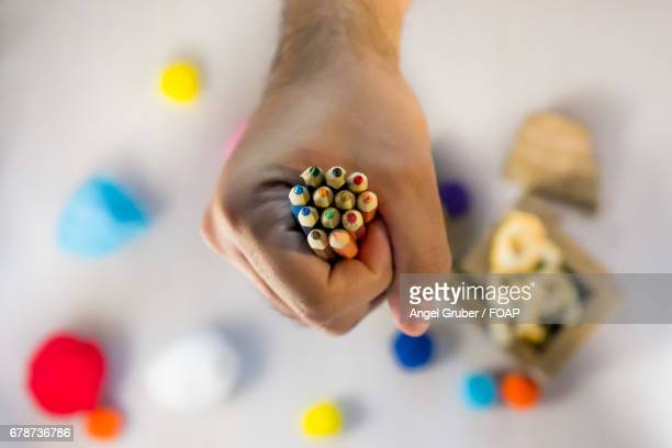 Hand holding colourful pencils