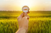 hand holding compass and rice field sunset.