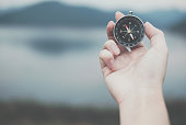 hand holding compass for searching direction outdoor. man seeking way with nature background. travel lifestyle & summer vacation concept