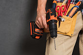 Close up of handyman holding a drill machine with tool belt around waist. Detail of artisan hand holding electric drill with tools isolated over grey background. Closeup hand of bricklayer holding car