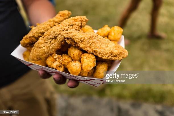 Hand holding container of fried chicken and potatoes