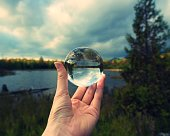 Hand holding crystal ball against horizon, and parklands of Maine