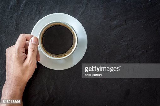 Hand holding cup of coffee  on black background : Stock-Foto