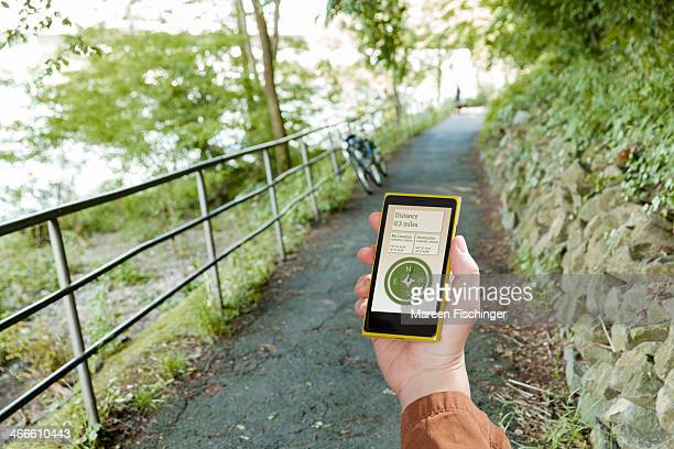 Hand holding device with compass app in nature