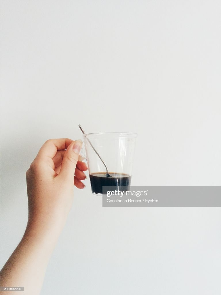 Hand holding espresso cup against white background