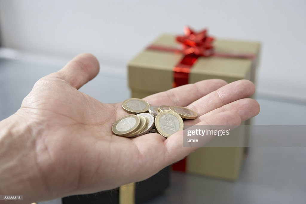 Hand holding Euro coins in front of gifts : Stock Photo