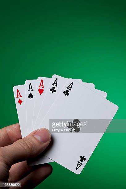 A hand holding five aces fanned out