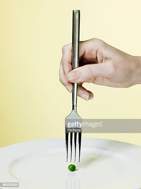 Hand holding fork above a pea
