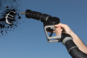 Hand holding Fuel hose spraying petrol oil in the shape of the Euro Symbol