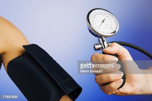 Hand holding gage for blood pressure device near patient's arm : Bildbanksbilder