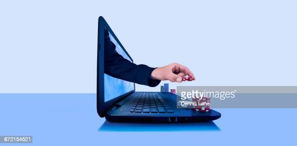 Hand holding gambling chips emerging from laptop screen