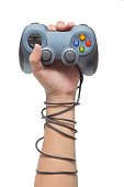 hand holding game controller and tied up with cables isolated on the white background