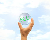Hand holding glass ball written 'ECO' against sky