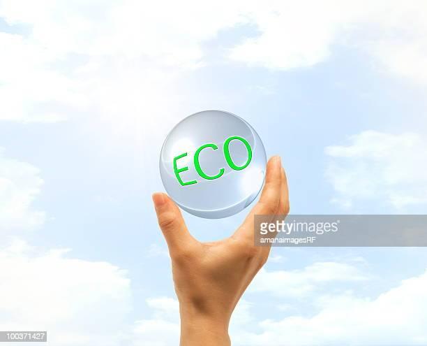 Hand holding glass ball written 'ECO' against sky
