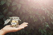 Hand holding glass jar with coins with SAVE label on green leaves background. Money saving for house, dream, vacation. Economic crisis and financial stability concept