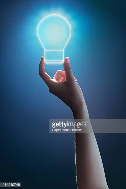 hand holding glowing light bulb studio background