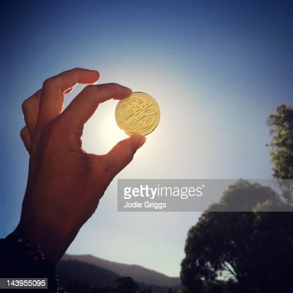 Hand holding gold coin up towards sun : Stock Photo