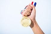 hand holding gold medal