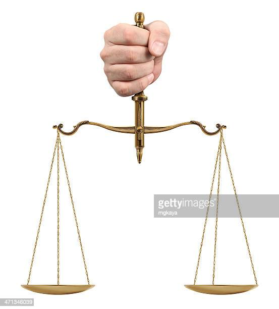 Hand holding gold scales on white background