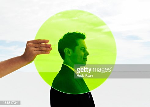 Hand holding green circle in fron of man's head. : Stock Photo