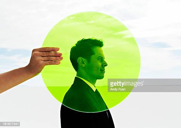 Hand holding green circle in fron of man's head.