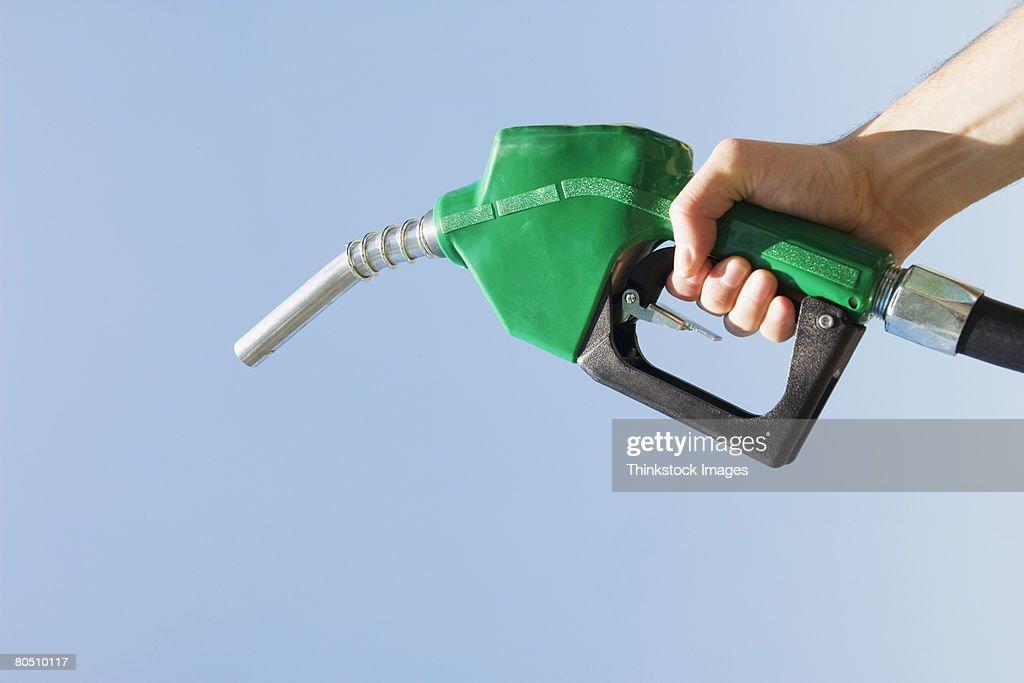 Hand holding green fuel pump nozzle