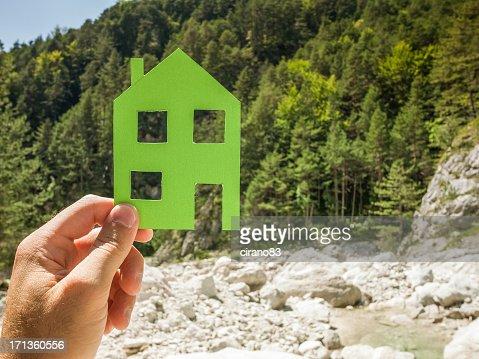 Main tenant la maison verte contre la nature