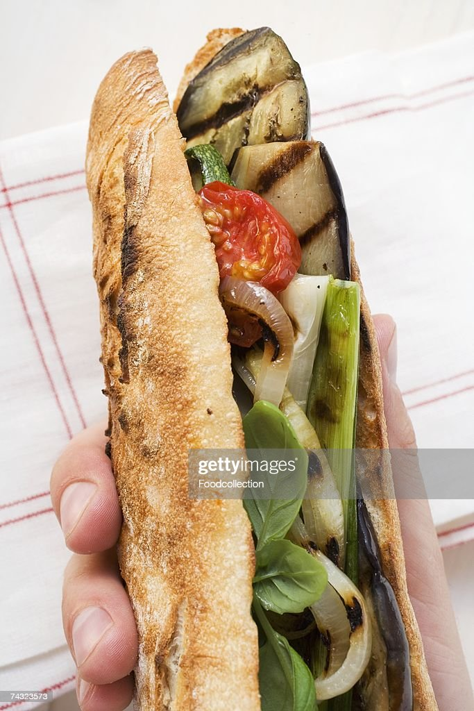 Hand holding grilled vegetables and basil in baguette : Stock Photo