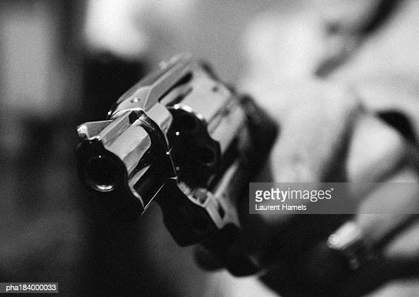 Hand holding gun, close-up, b&w