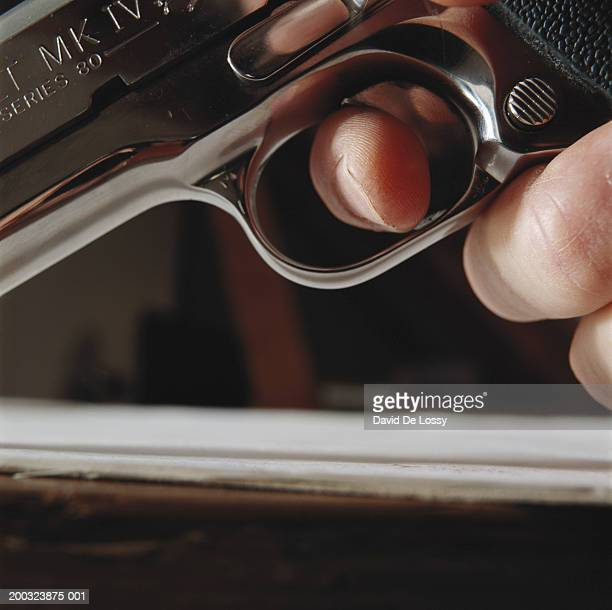 Hand holding gun, close-up, low angle view