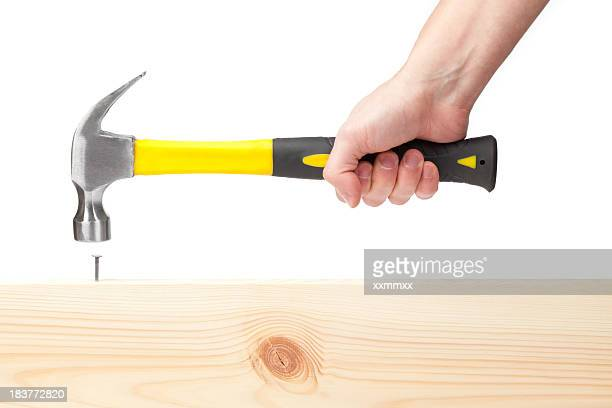 Hand holding hammer hitting a nail in wood