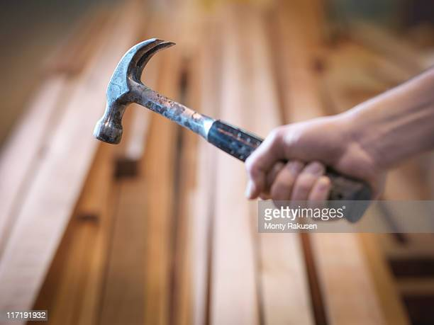Hand holding hammer next to timber